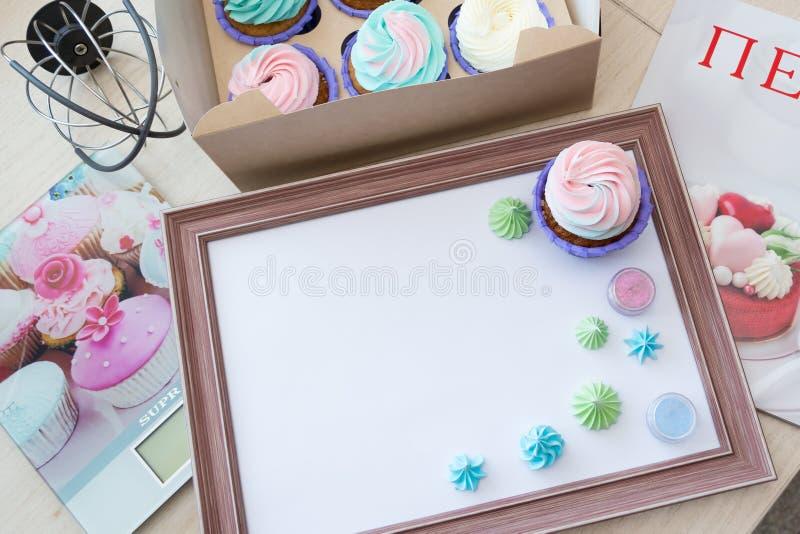 Cadre en bois avec la feuille blanche autour de la meringue et du petit gâteau avec de la crème multicolore, échelle de cuisine,  image libre de droits