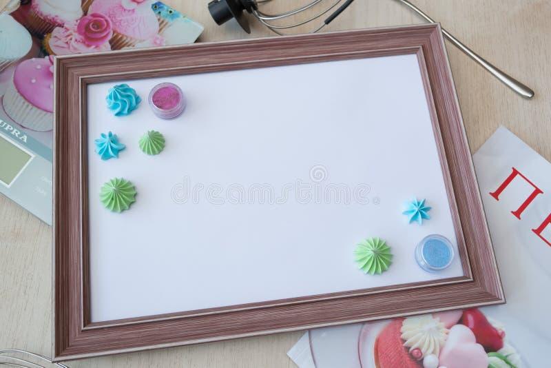 Cadre en bois avec la feuille blanche autour de la meringue et du petit gâteau avec de la crème multicolore, échelle de cuisine,  photographie stock