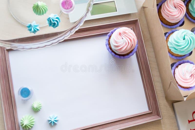 Cadre en bois avec la feuille blanche autour de la meringue et du petit gâteau avec de la crème multicolore, échelle de cuisine,  image stock