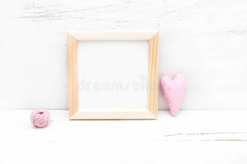 Cadre en bois carré et coeur rose sur un fond en bois moquerie photos libres de droits