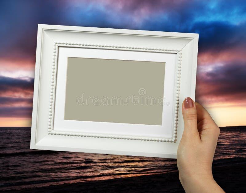 Cadre en bois chez des mains de la femme Coucher du soleil sur le fond image stock