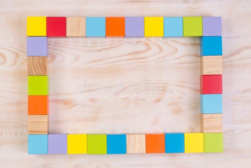 Cadre en bois coloré de blocs sur le fond en bois blanc, vue supérieure avec l'espace de copie photographie stock
