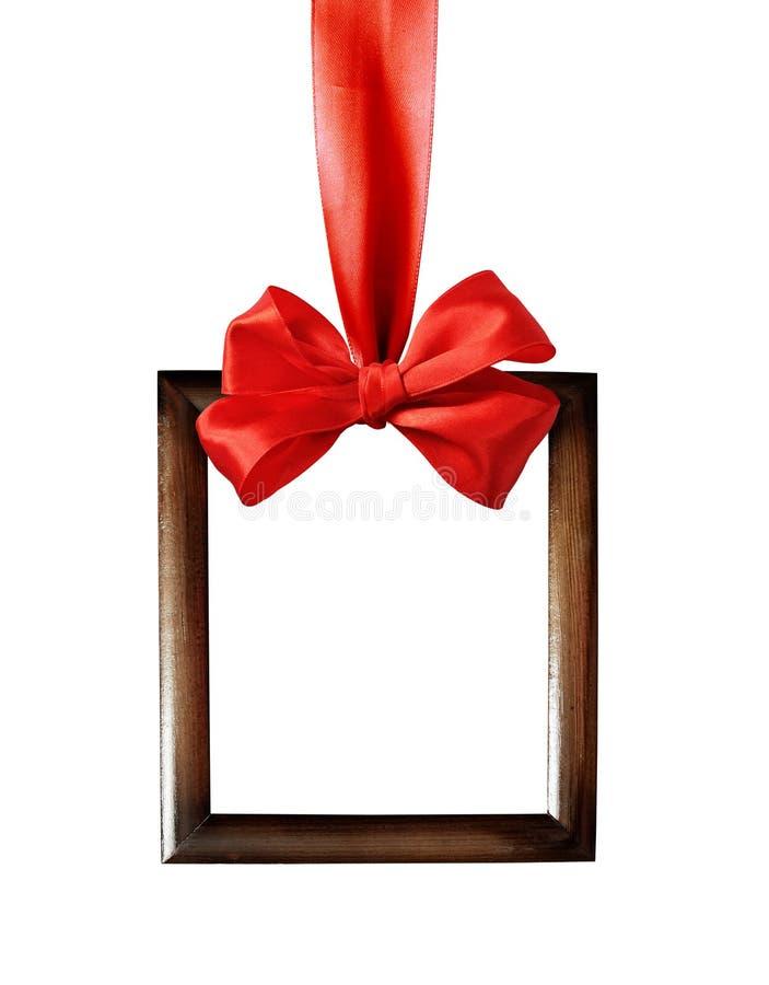 Cadre en bois de Brown accrochant sur le ruban rouge de satin avec l'arc photographie stock