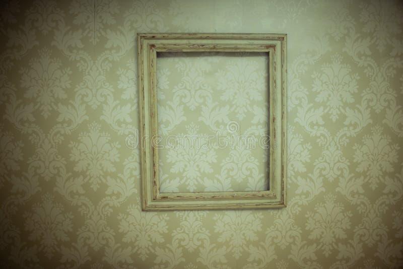 Cadre en bois de vintage vide accrochant sur le papier peint photographie stock