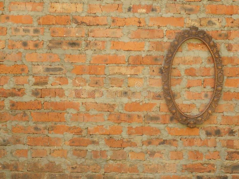 Cadre en bronze ovale sur le fond d'un vieux mur de briques photographie stock libre de droits