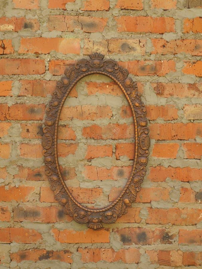 Cadre en bronze ovale sur le fond d'un vieux mur de briques photos libres de droits