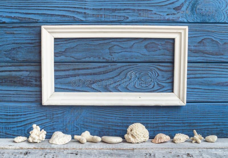 Cadre et coquilles blancs sur un fond des conseils bleus photo stock