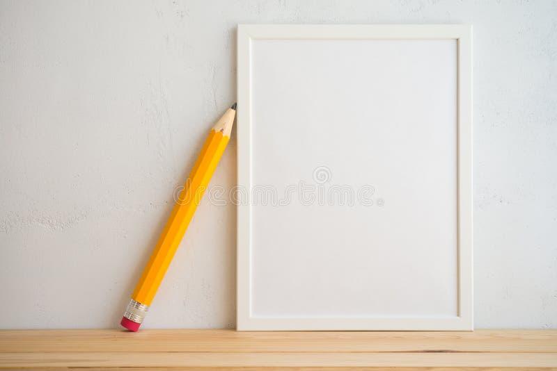 Cadre et crayon de photo sur le fond blanc de mur, idées créatives photos stock