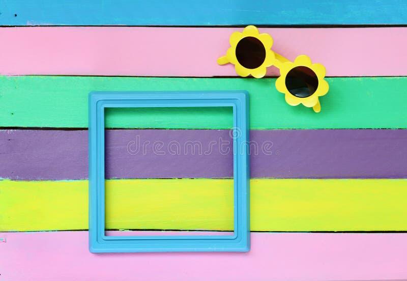 Cadre et lunettes de soleil de photo sur le fond en bois coloré photographie stock libre de droits