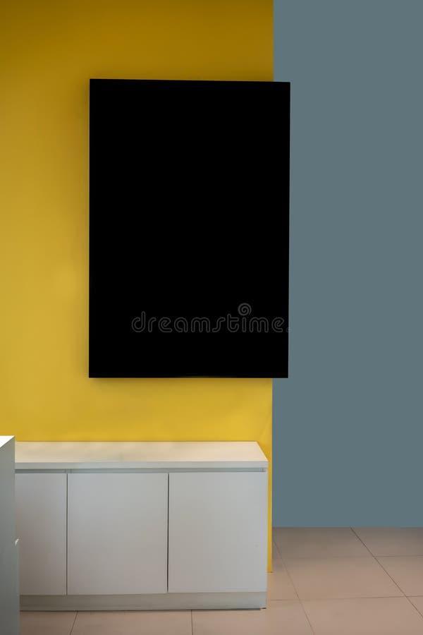 Cadre noir de maquette accrochant sur le mur jaune dans l'intérieur moderne image stock