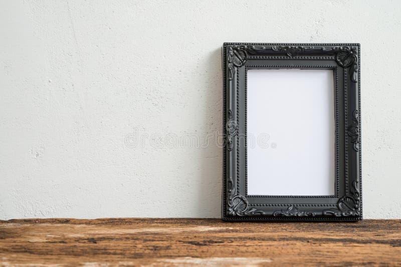 Cadre noir de photo de vintage sur la vieille table en bois au-dessus du Ba blanc de mur image stock
