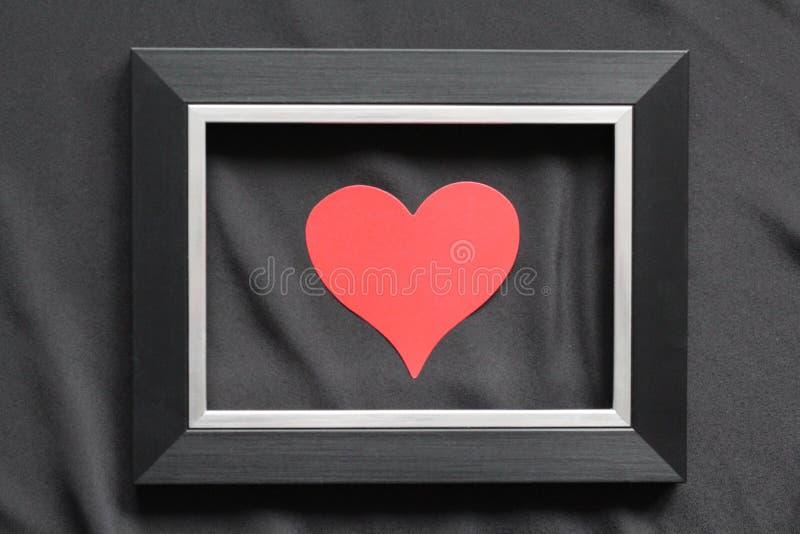 Cadre noir sur un fond noir, près du coeur catégoriquement photo libre de droits