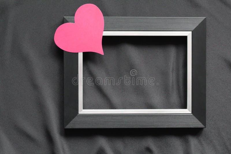 Cadre noir sur un fond noir, près du coeur catégoriquement photographie stock