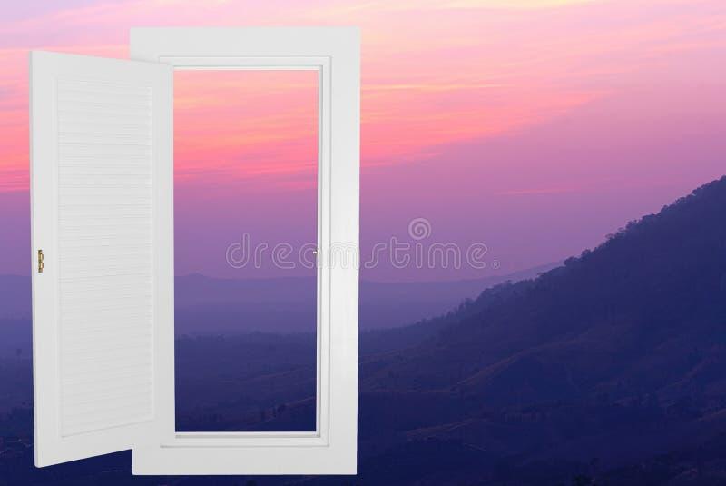 Cadre ouvert blanc de fenêtre avec le fond de moutain de coucher du soleil photos stock