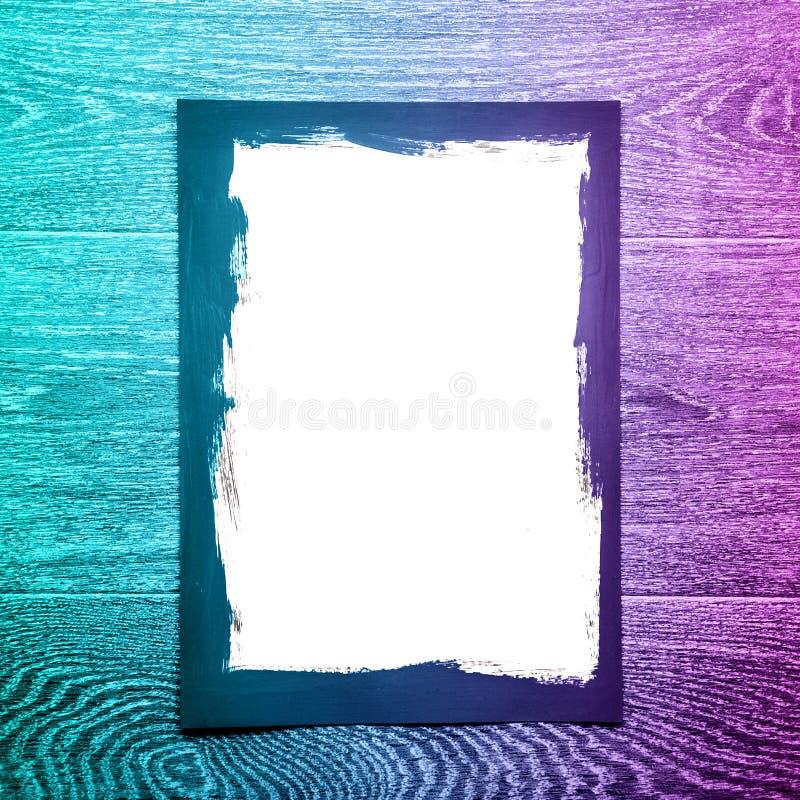 Cadre peint noir sur le livre blanc sur le fond en bois avec la lampe au néon photos libres de droits
