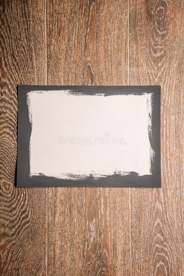 Cadre peint noir sur le livre blanc sur le fond en bois photographie stock