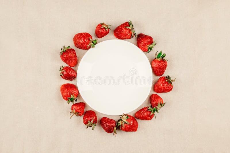Cadre rond de fraise et plat blanc vide sur le fond de papier de métier, vue supérieure, maquette étendue plate de baies La vue a photos stock