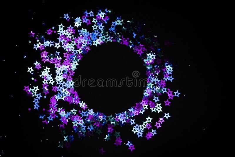 Cadre rond fait de confettis olographes colorés d'étoiles sur le fond noir Concept de fête et de vacances images libres de droits