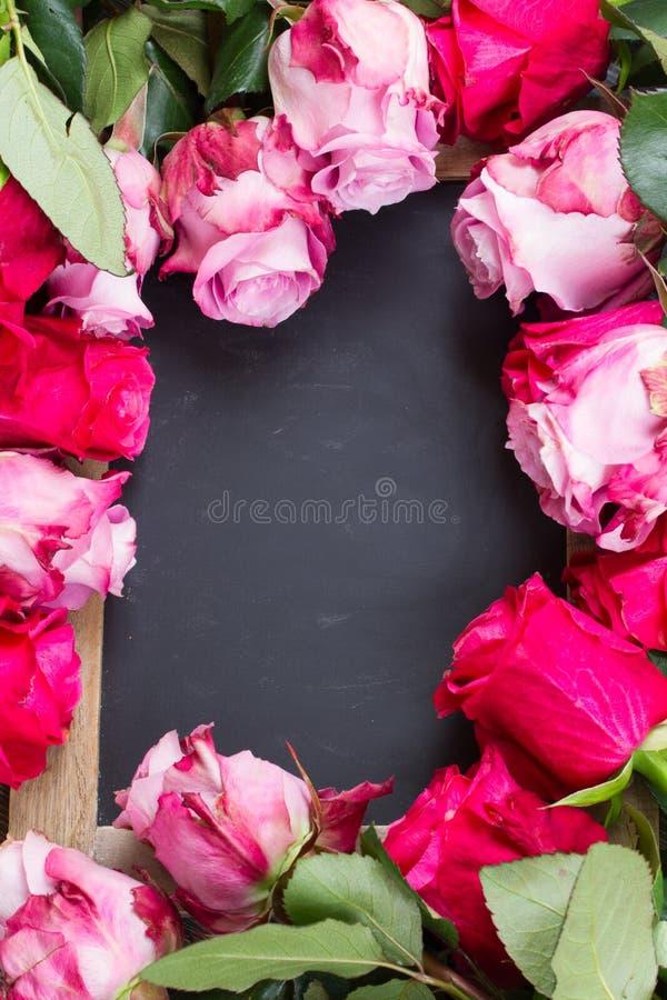 Cadre rouge et rose de roses sur la table photo stock