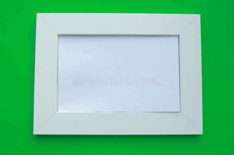 Cadre vide blanc avec l'espace pour des mensonges des textes sur un fond vert photographie stock