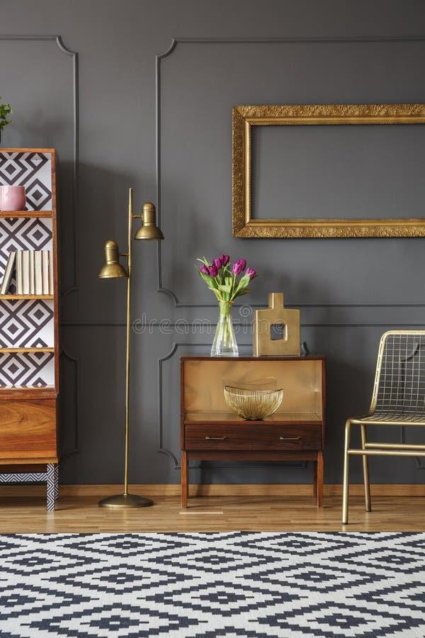 Cadre vide d'or accrochant sur le mur avec le bâti au-dessus du rétro Cu image stock