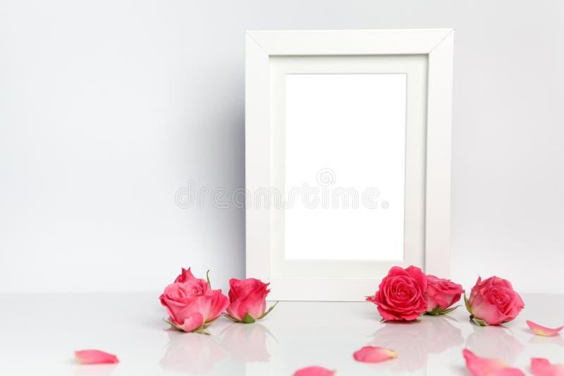 Cadre vide de photo et roses roses sur le fond blanc de table photos stock