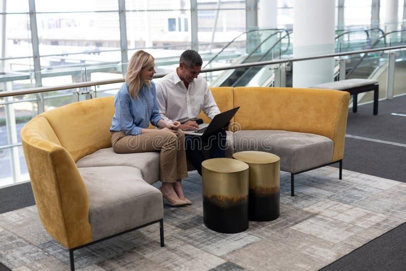 Cadres commerciaux de Caucasiens à l'aide de l'ordinateur portable sur le sofa photographie stock