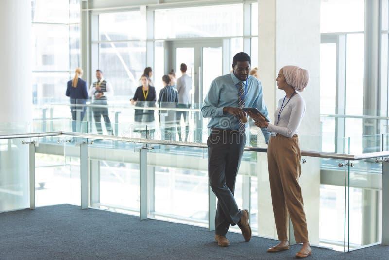 Cadres commerciaux discutant au-dessus du comprimé numérique dans le bureau image libre de droits