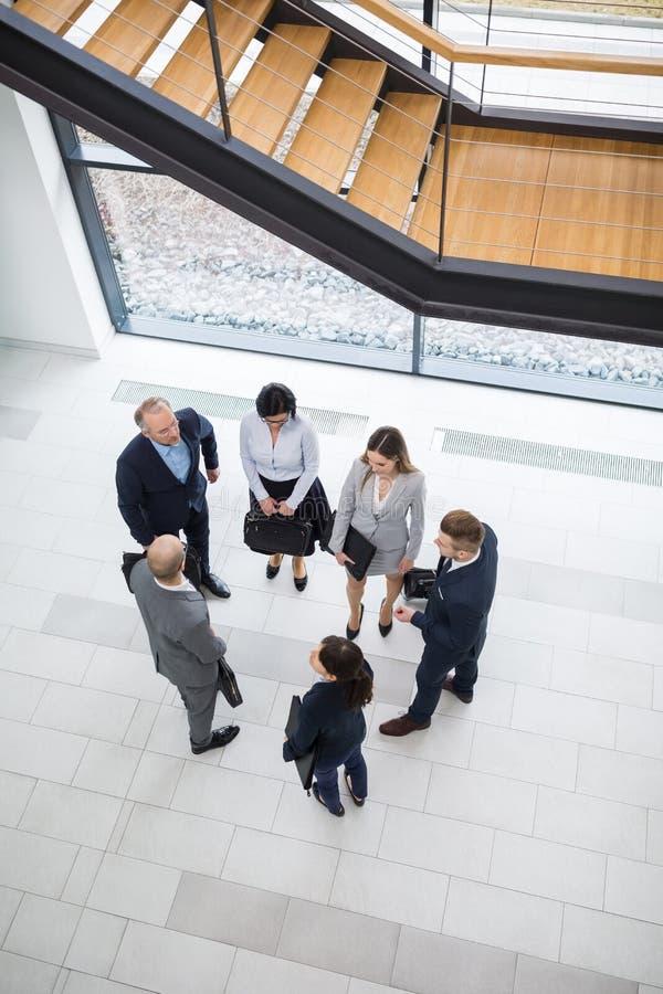 Cadres commerciaux discutant dans le lobby de bureau photos stock