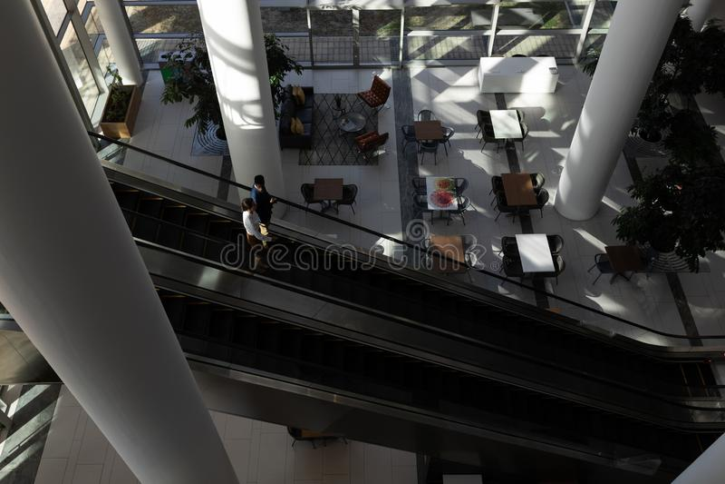 Cadres commerciaux multi-ethniques employant l'escalator dans le bureau photos libres de droits