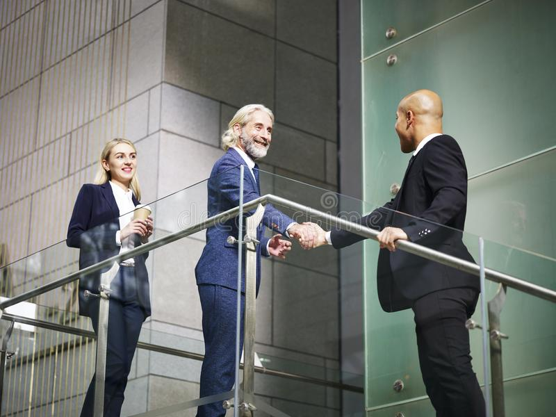 Cadres d'entreprise se serrant la main dans l'immeuble de bureaux moderne images libres de droits