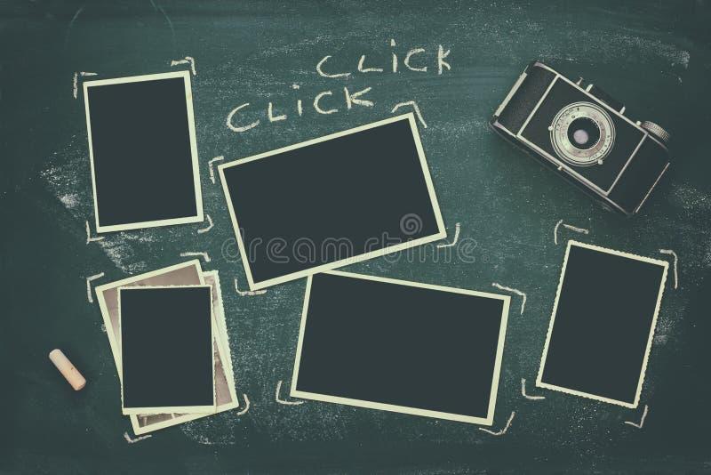 cadres de photo à côté de vieil appareil-photo au-dessus de tableau noir image stock