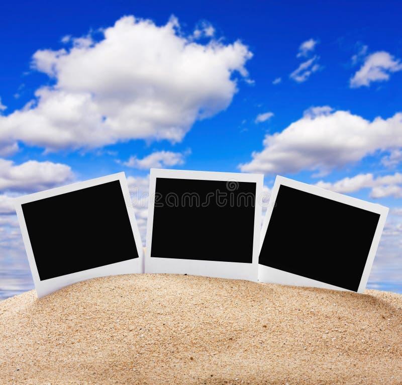 Cadres de photos dans le sable contre le ciel images stock