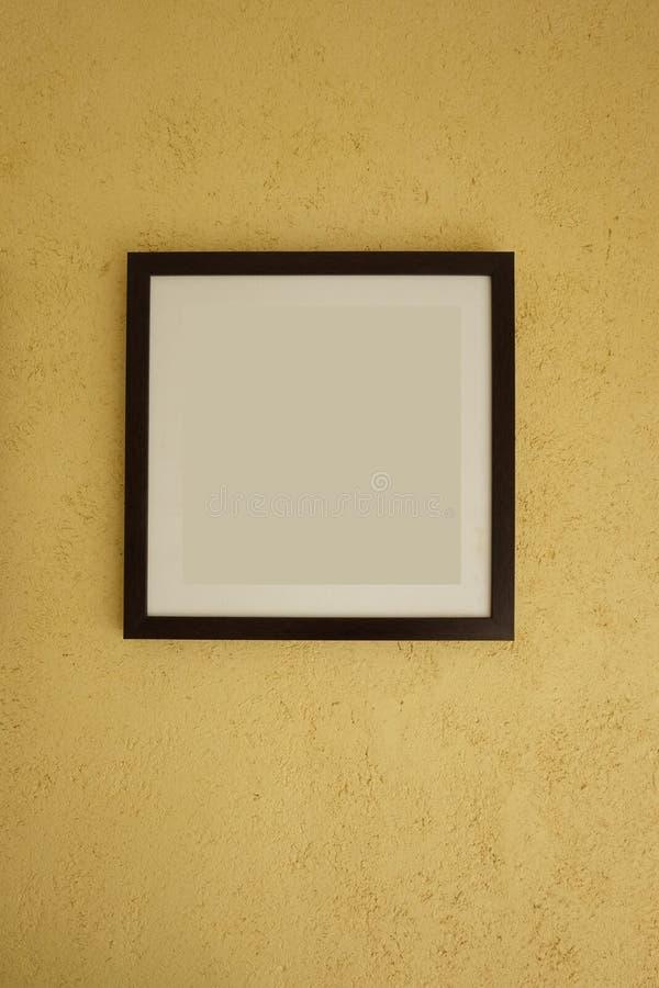 Cadres de tableau vides sur les murs jaunes de cru photographie stock