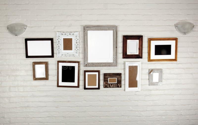 Cadres et lampes vides sur le mur mis en sac par blanc photo stock