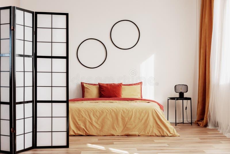 Cadres noirs ronds sur le mur blanc de la chambre à coucher élégante intérieur avec le lit grand avec le jaune et la literie de g photographie stock libre de droits