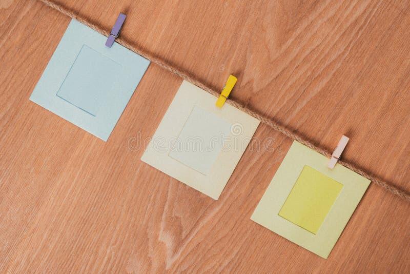 Cadres vides de photo sur la table en bois Concept de cru Trois cadres carrés sur la corde photos libres de droits