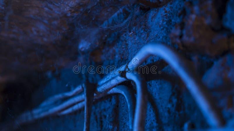 Caduta dei cavi elettrici sotto il soffitto in cantina fotografia stock