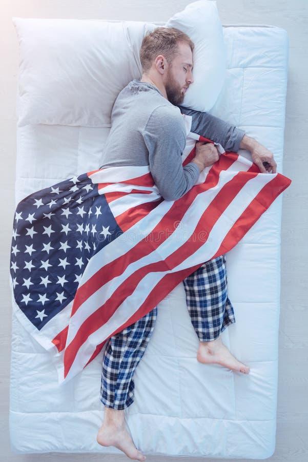 Caduta del giovane addormentata con la bandiera degli S.U.A. in mani immagini stock