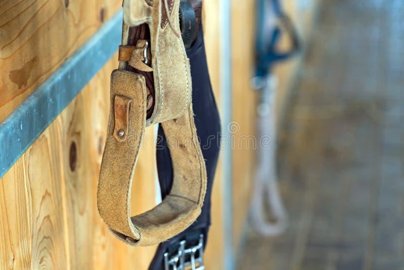 Caduta dell'attrezzatura del cavallo da equitazione della staffa del primo piano sul recinto di legno fotografia stock