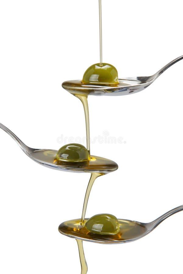 Caduta dell'olio di oliva e dei cucchiai immagine stock libera da diritti