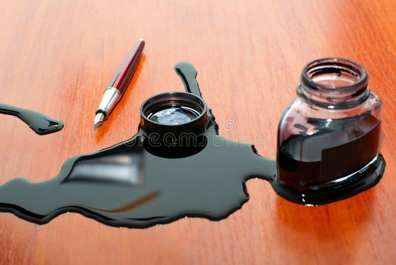 Caduta nera dell'inchiostro vicino alla penna rossa sulla tabella fotografie stock libere da diritti