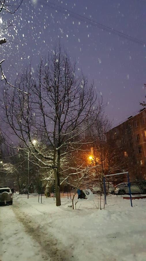 Cadute della neve, la città splende immagine stock