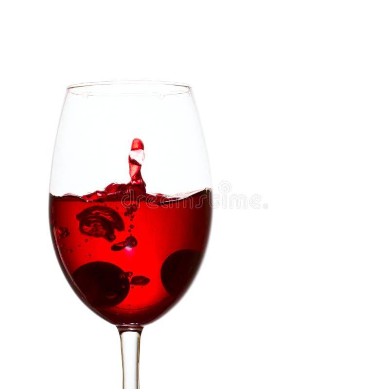 Caduto in un vetro dell'uva ha formato una spruzzata di vino rosso immagine stock libera da diritti