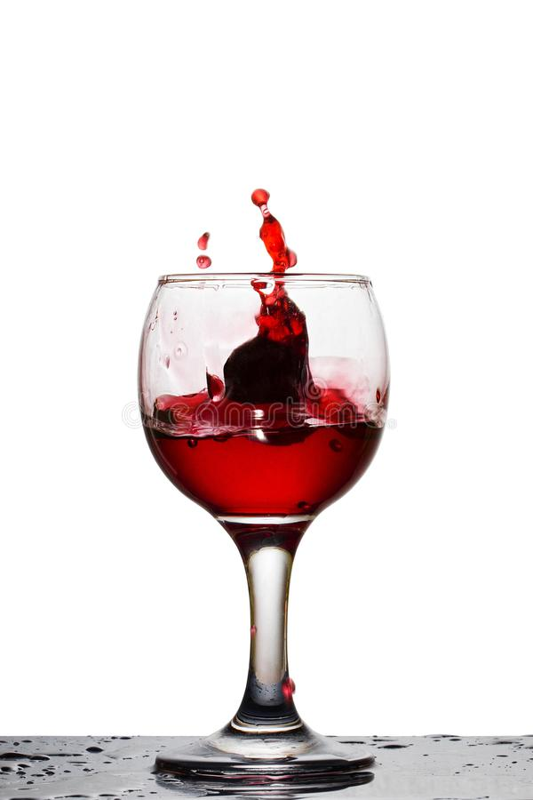Caduto in un vetro dell'uva ha formato una spruzzata di vino rosso luminoso immagine stock