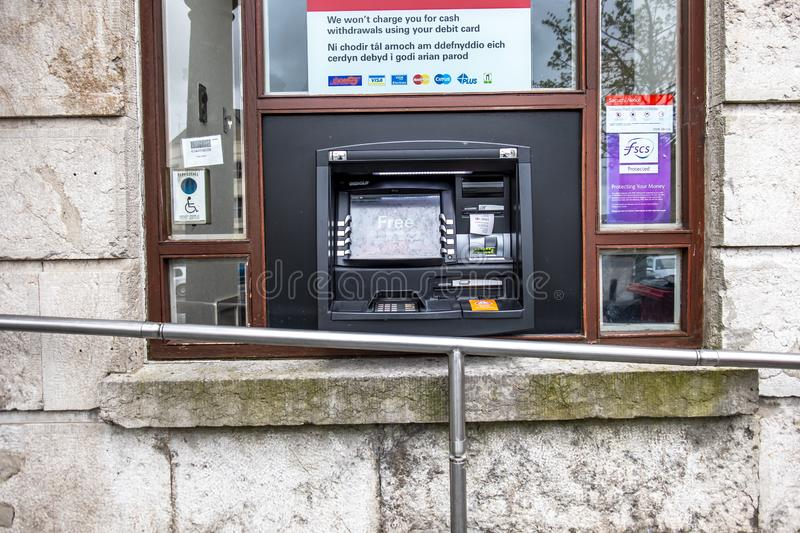 Caernarfon , Wales - May 01 2018 : Cash machine of the HSBC Bank on a windy day in the rain.  royalty free stock photo