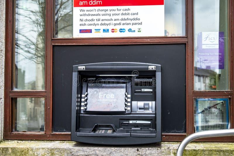 Caernarfon , Wales - May 01 2018 : Cash machine of the HSBC Bank on a windy day in the rain.  stock photos