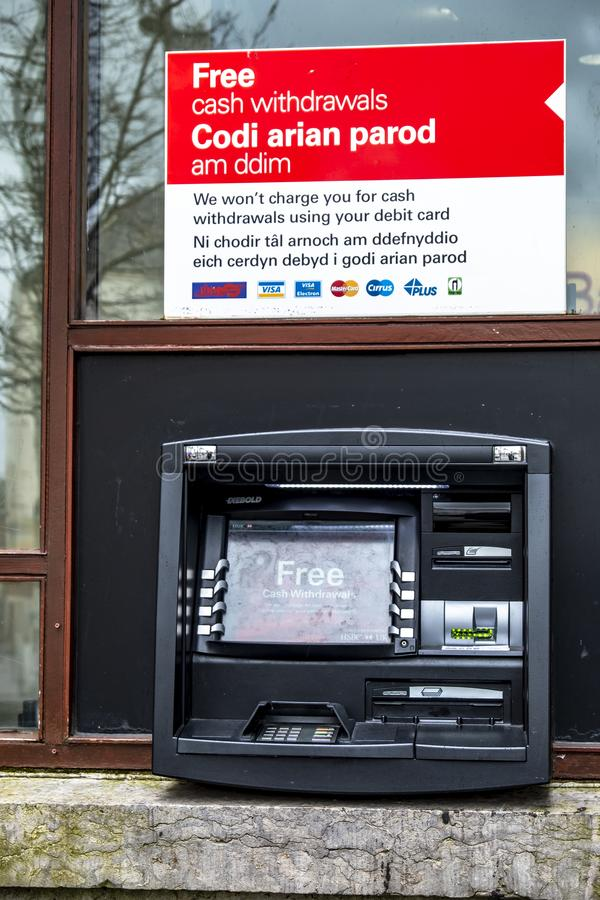 Caernarfon , Wales - May 01 2018 : Cash machine of the HSBC Bank on a windy day in the rain.  royalty free stock images