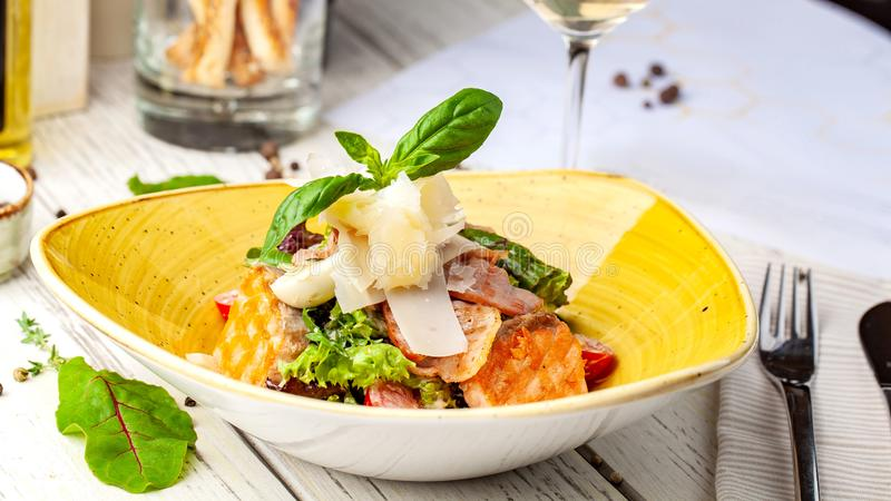 caesar σολομός σαλάτας μίγμα των σαλατών, ντομάτες κερασιών, τυρί παρμεζάνας, βασιλικός Ένα πιάτο σε ένα κεραμικό πιάτο είναι στο στοκ φωτογραφία με δικαίωμα ελεύθερης χρήσης