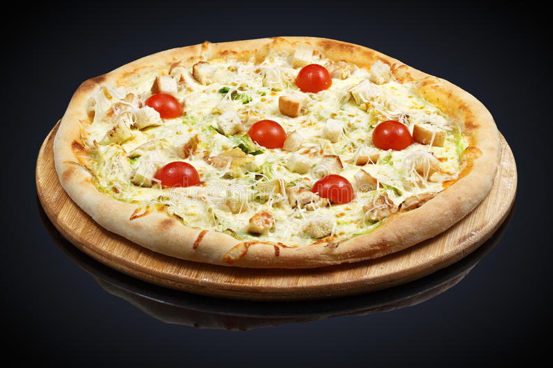 Caesar Pizza tomatoes with chicken. On a black background royalty free stock photo
